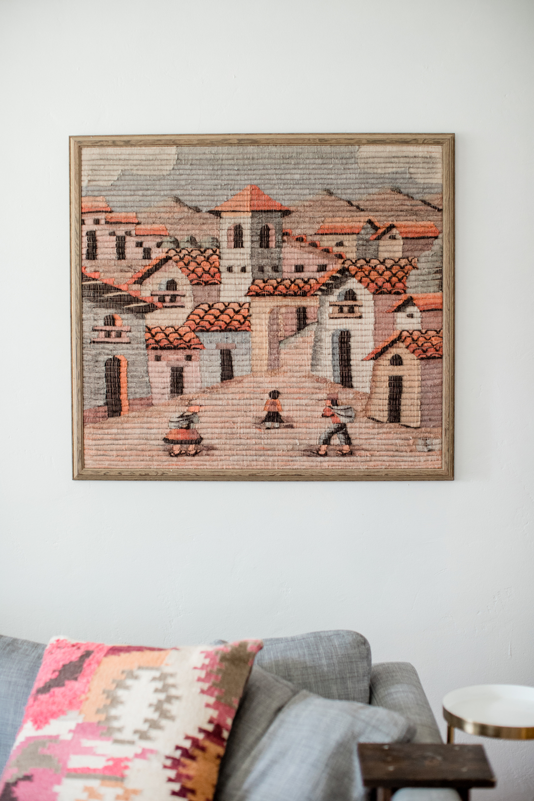 woven wall art of small town with tiled roofs