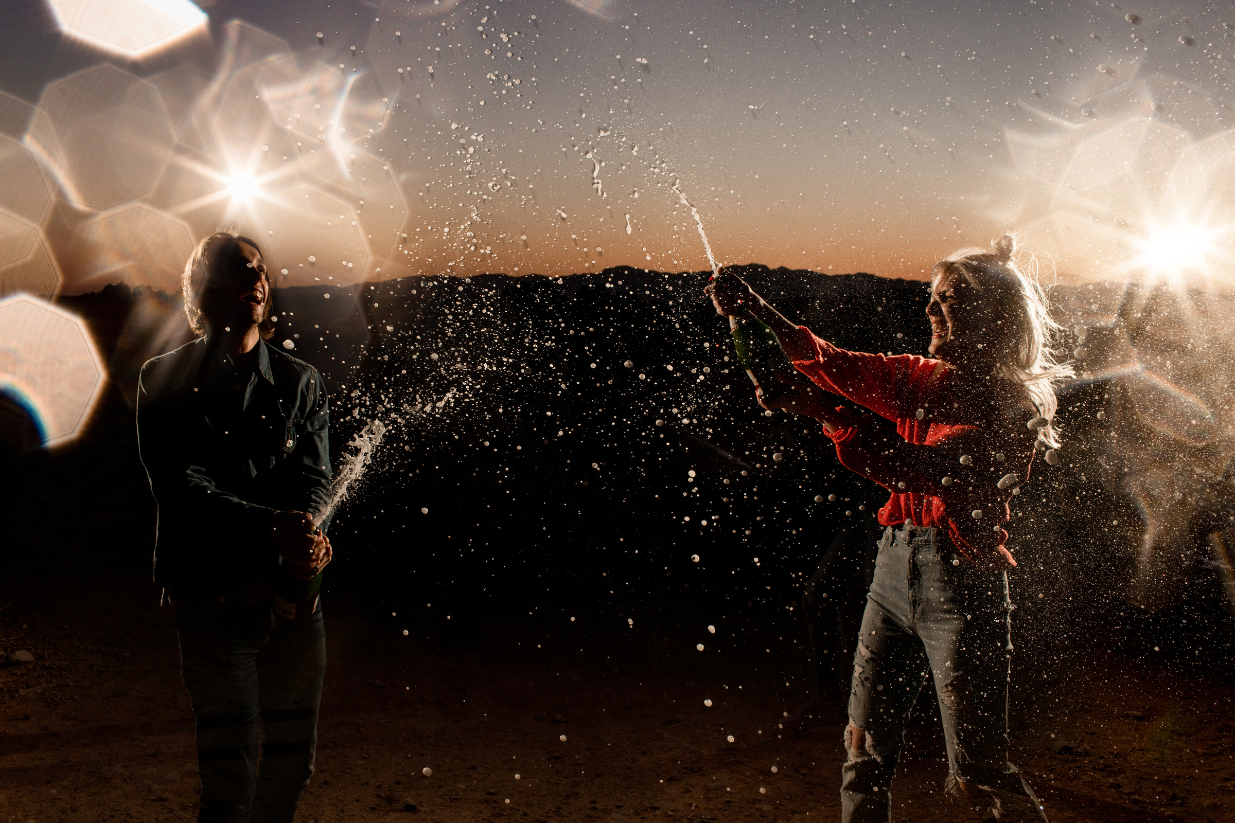 couple popping champagne corks with lights around them