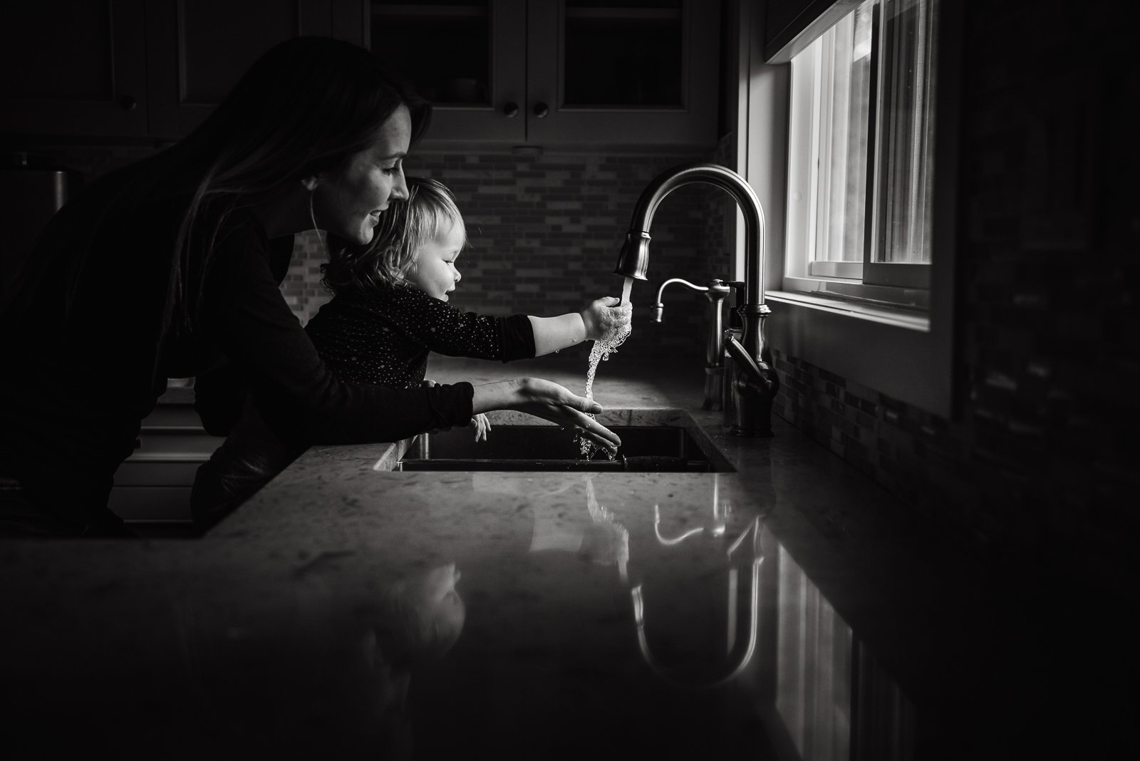 Mother helping child wash hands