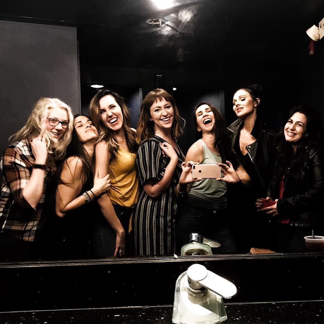 seven women taking a self portrait in bathroom mirror