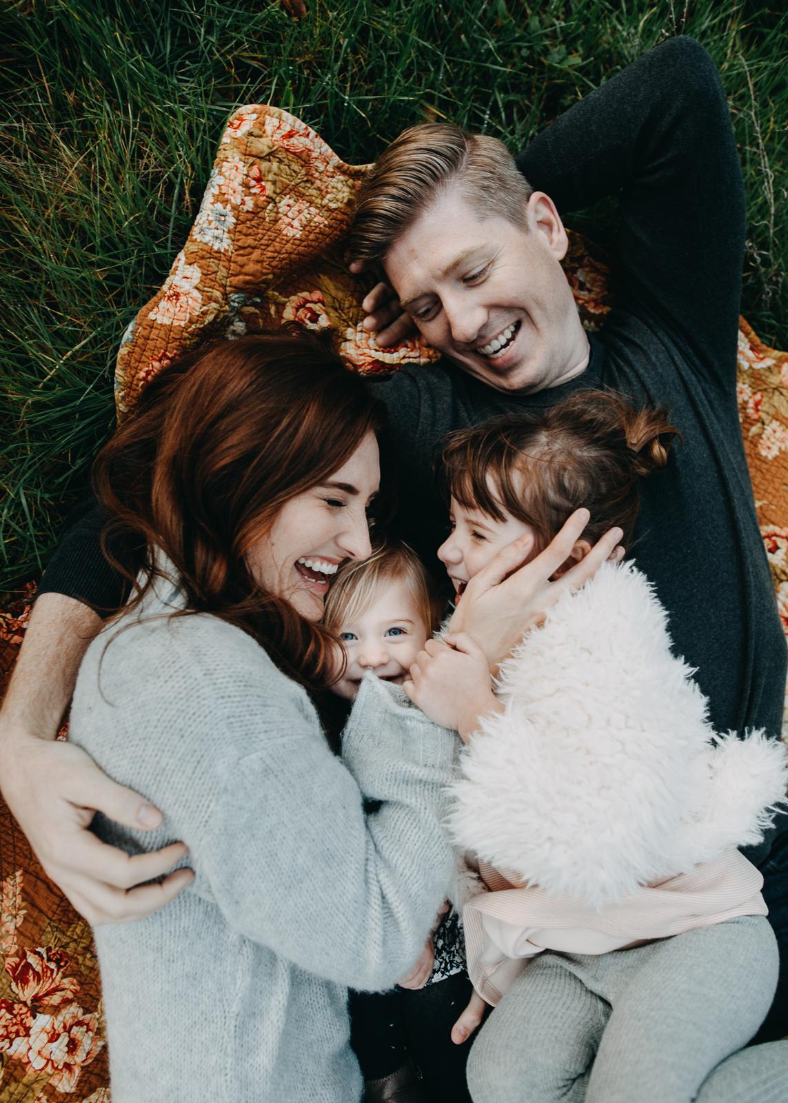 family hugging on blanket in grass