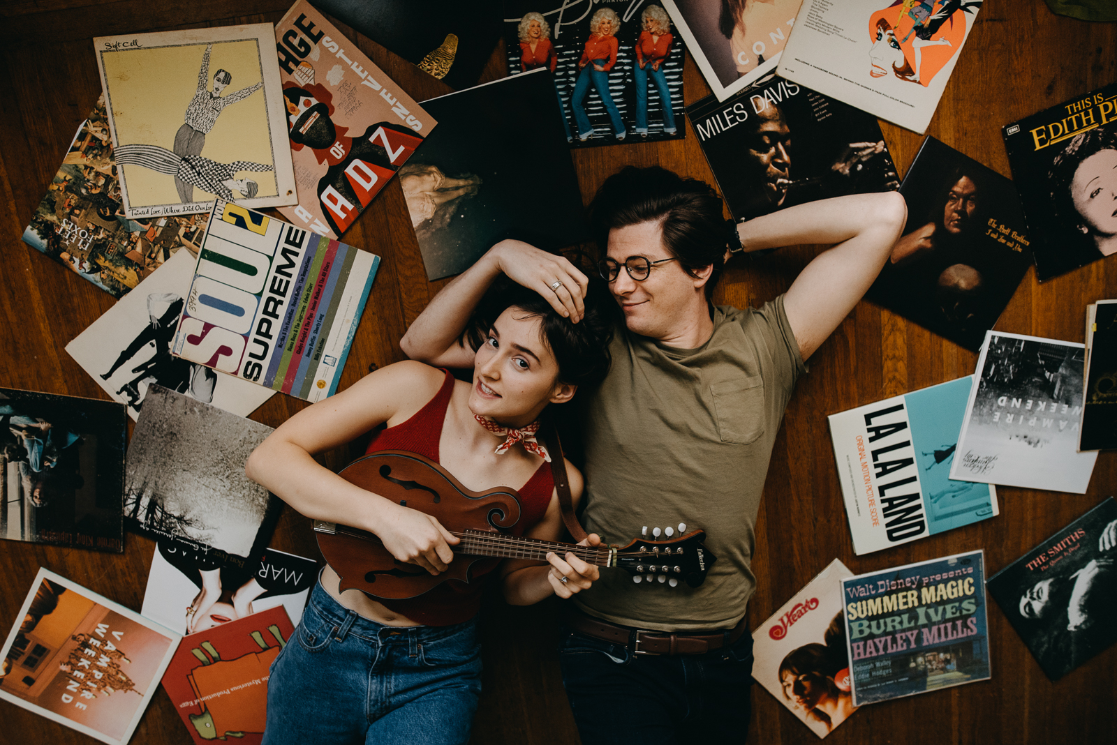 man and woman with ukulele laying on floor covered in albums