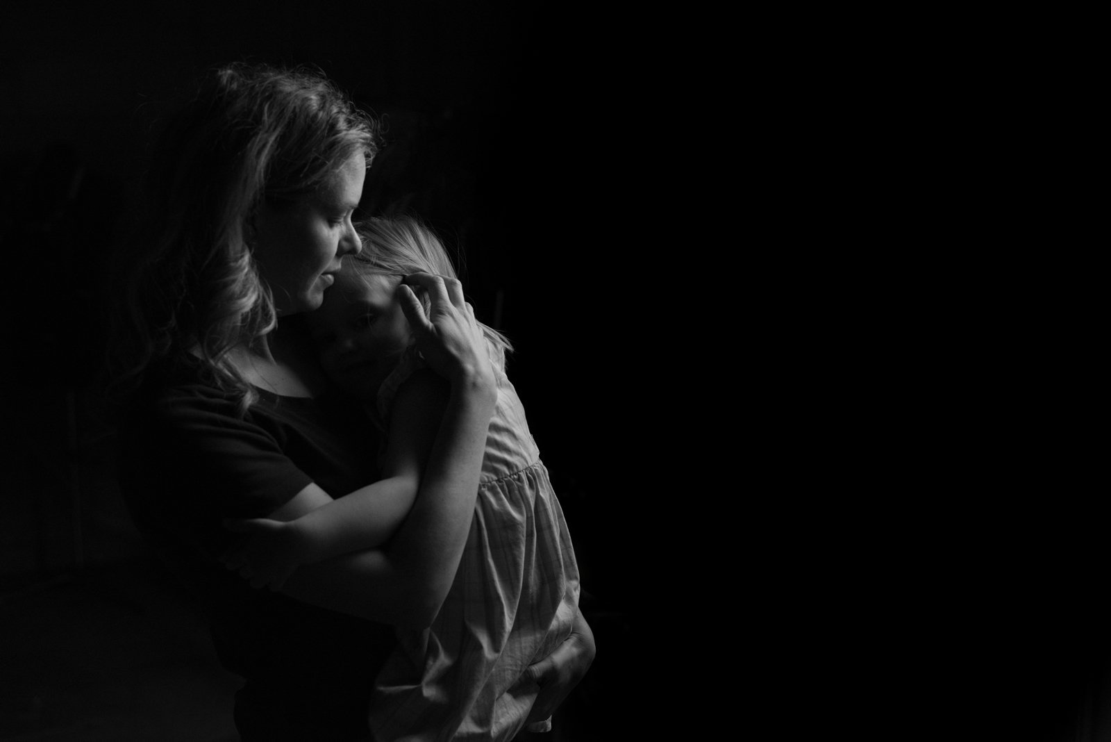 mother hugging daughter in low light