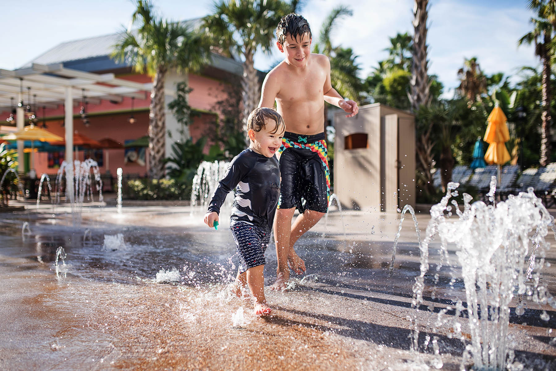 two boys playing in water fountains