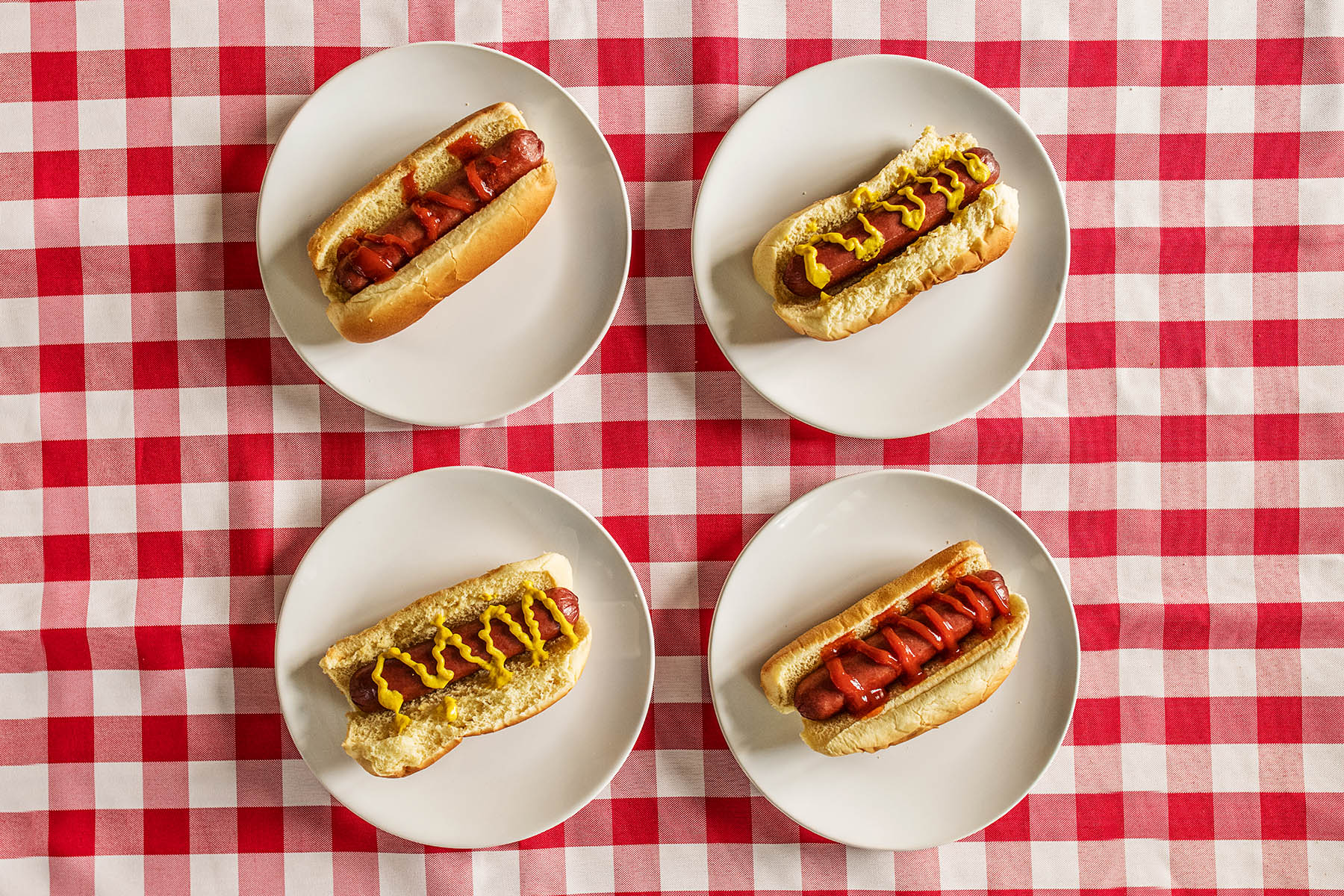 four hot dogs on red and white checked table cloth