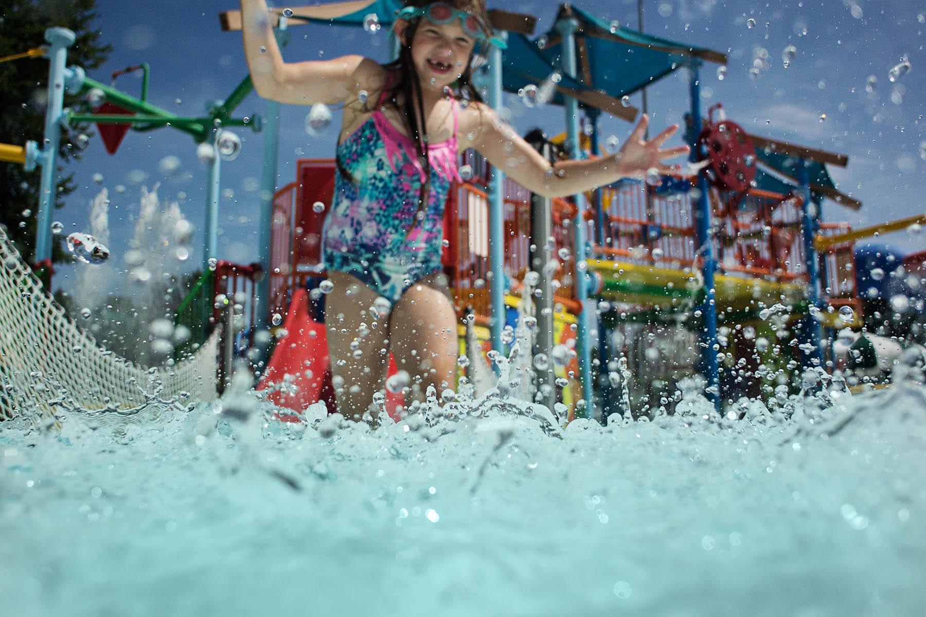 girl running through pool splashing water