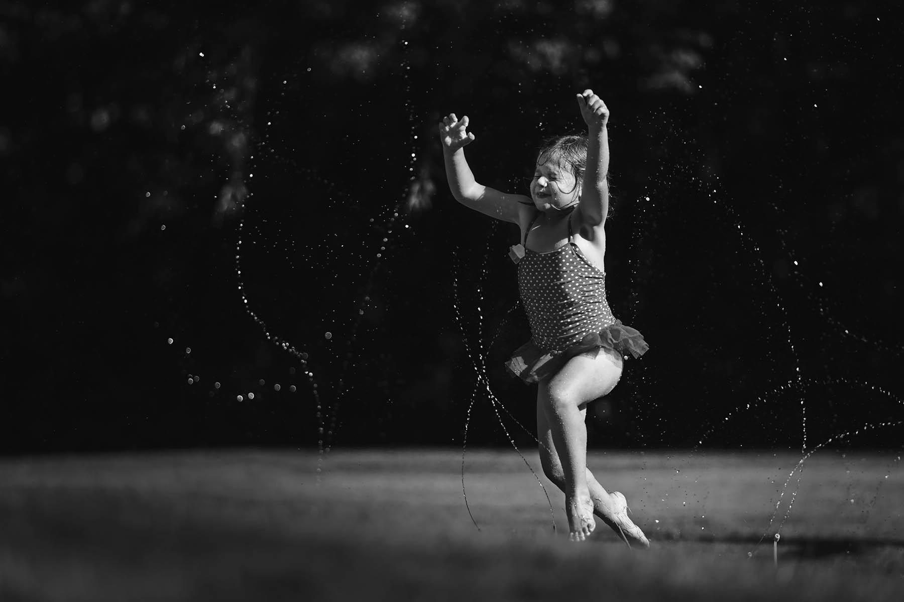 black and white photo of girl running through sprinkler