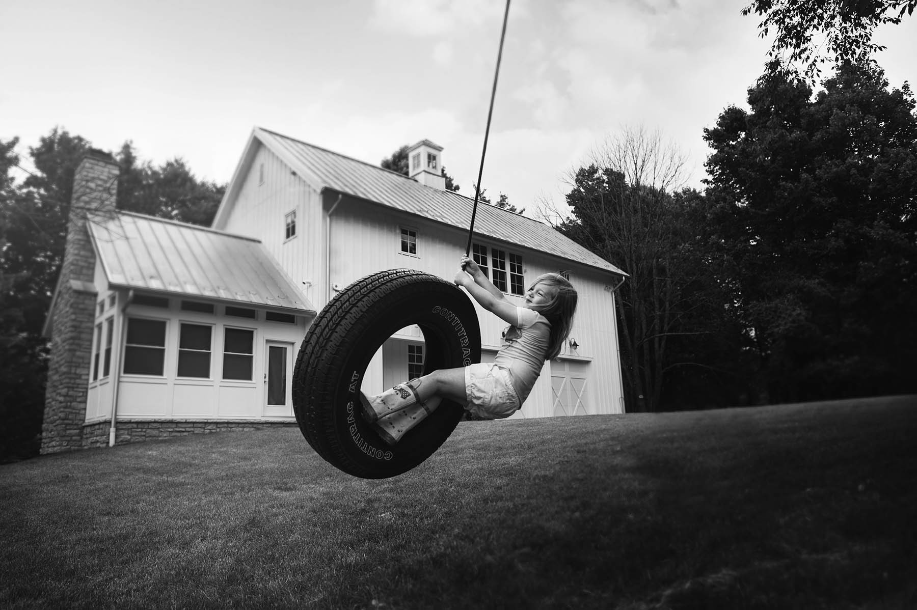 black and white photo of girl on tire swing