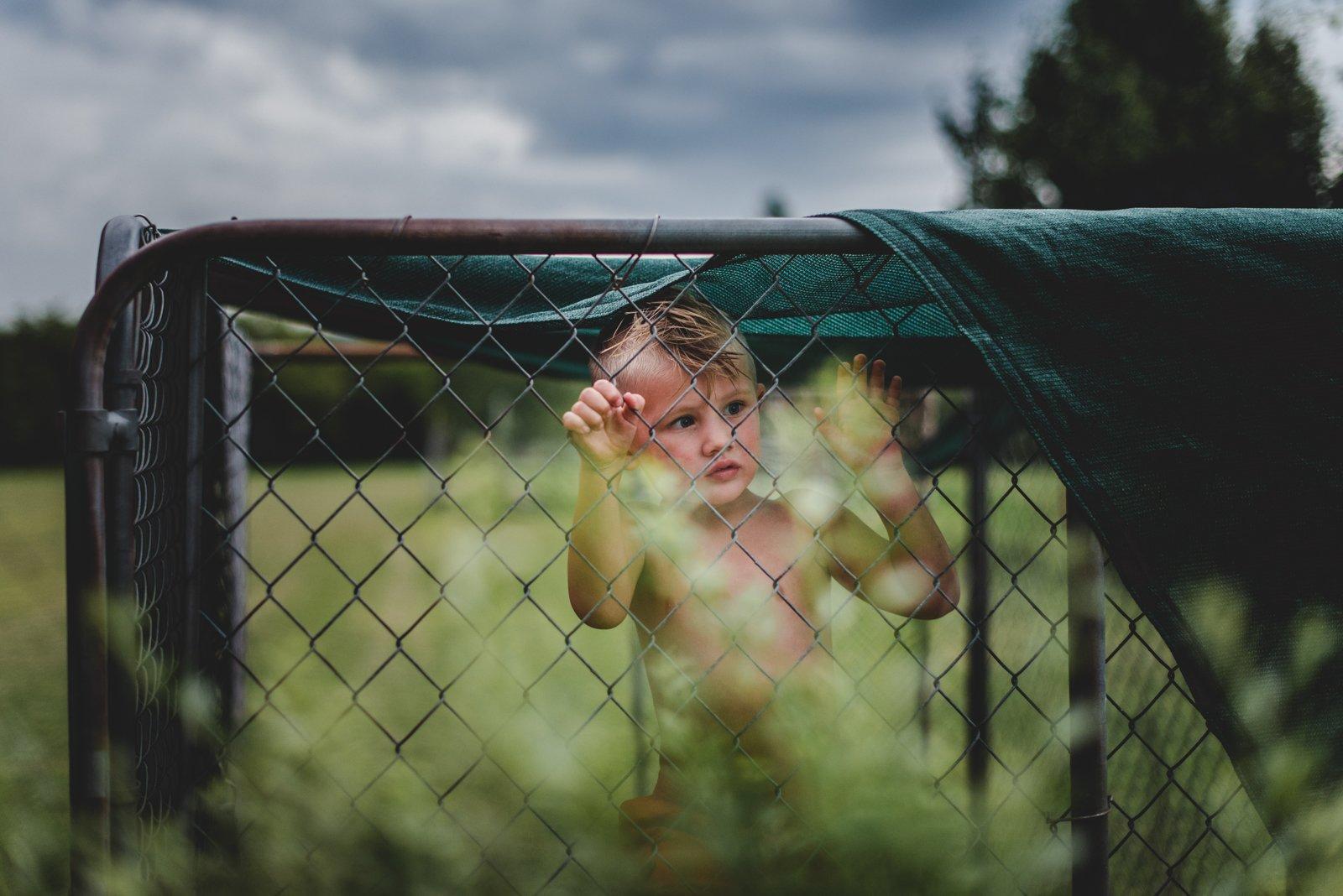 boy-standing-at-fence-natalie-greenroyd-50mm-lens