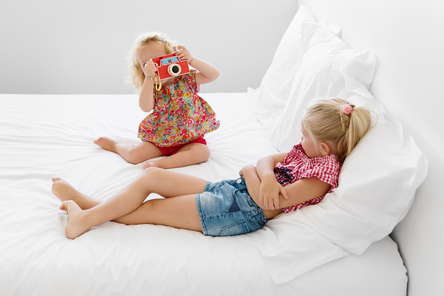 kids-on-bed-playing-with-toy-camera-by-lisa-tichane