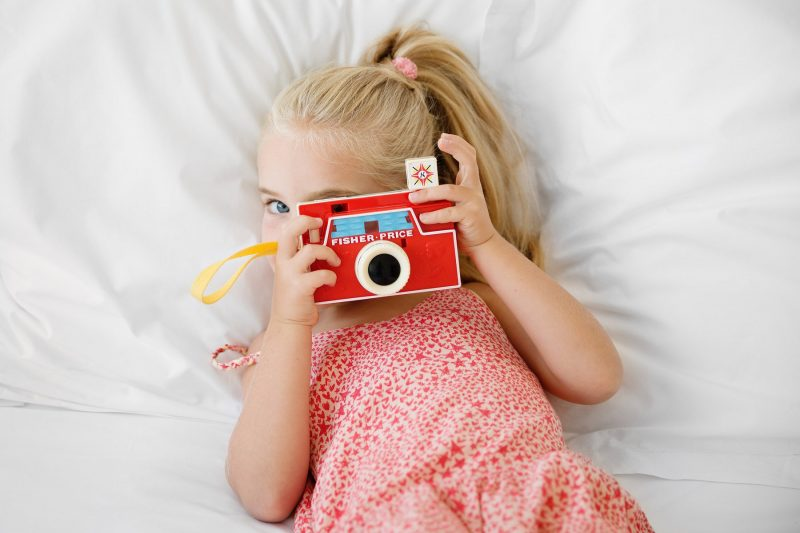 girl-laying-on-bed-taking-pictures-with-toy-camera-by-lisa-tichane