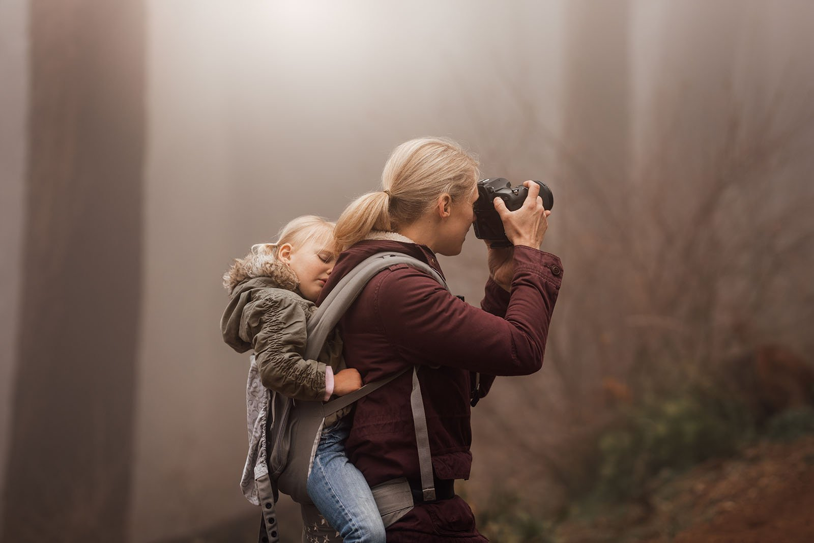 woman-taking-pictures-with-girl-asleep-in-backpack-by-meg-loeks