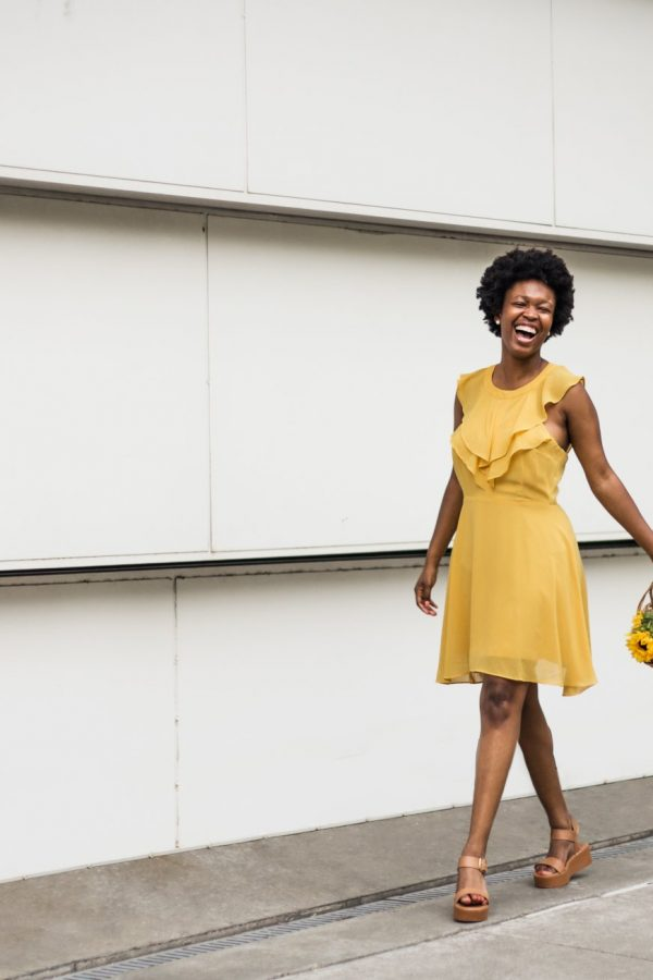 woman-yellow-dress-holding-flowers-laughing-chanel-french-50mm-lens