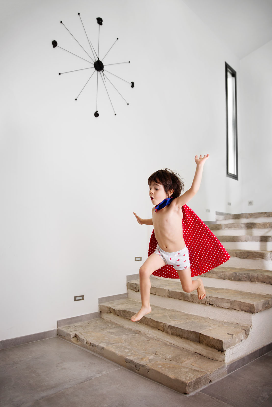child-with-red-cape-leaping-down-stairs-lisa-tichane