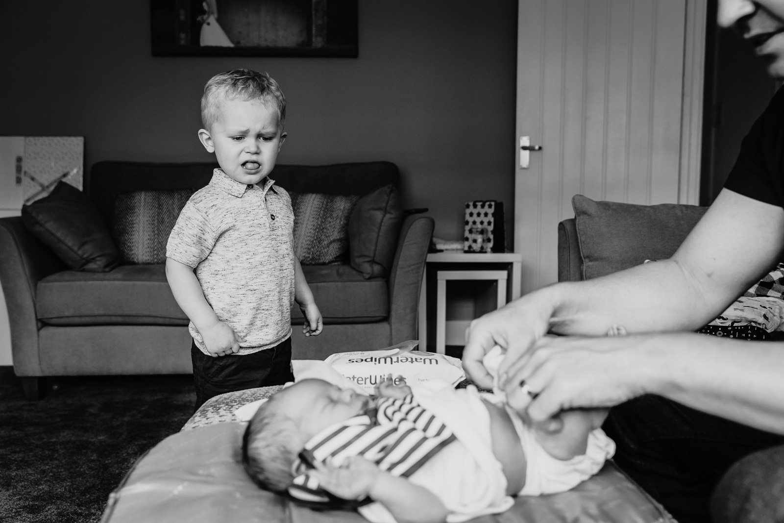 Alina Clark_alinaclark black and white photo of brother watching baby get diaper changed