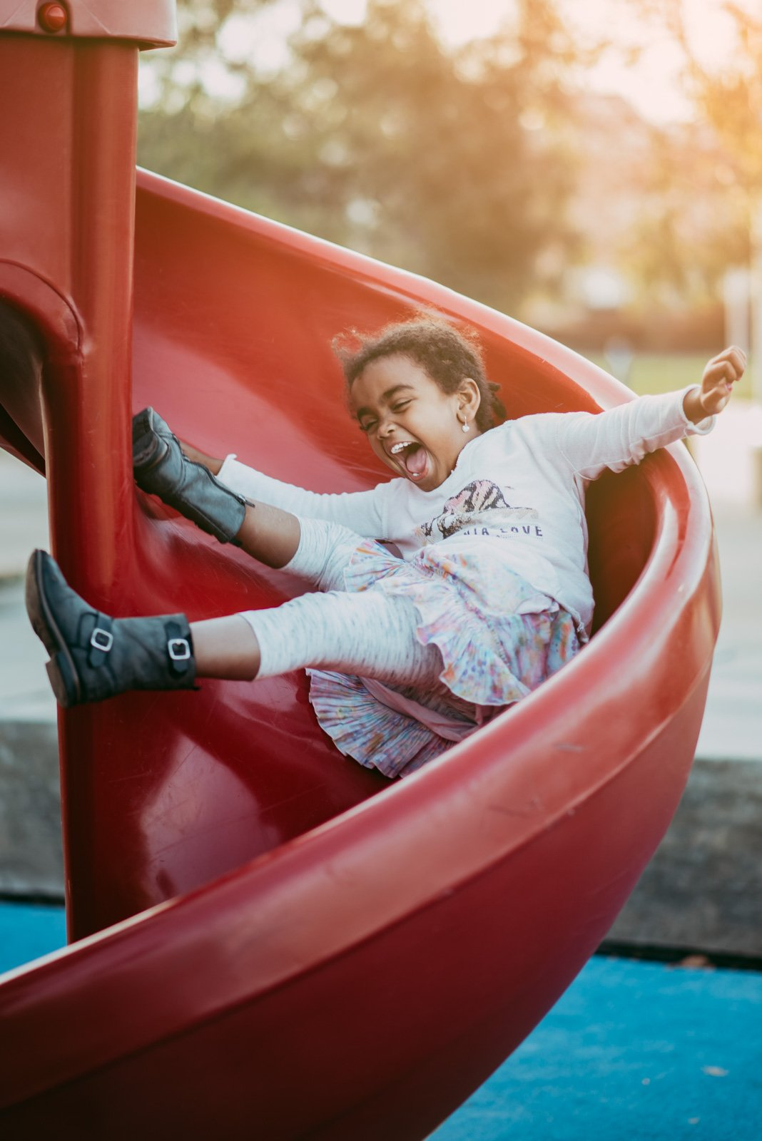 Christine Ekeroth_cjoyekeroth clickin moms march forum photo contest girl sliding down slide at playground