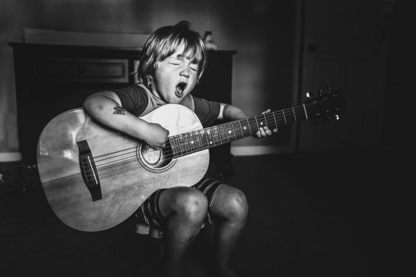 Dustyn Yonke_dyonke clickin moms march forum photo contest young boy playing guitar singing with eyes closed