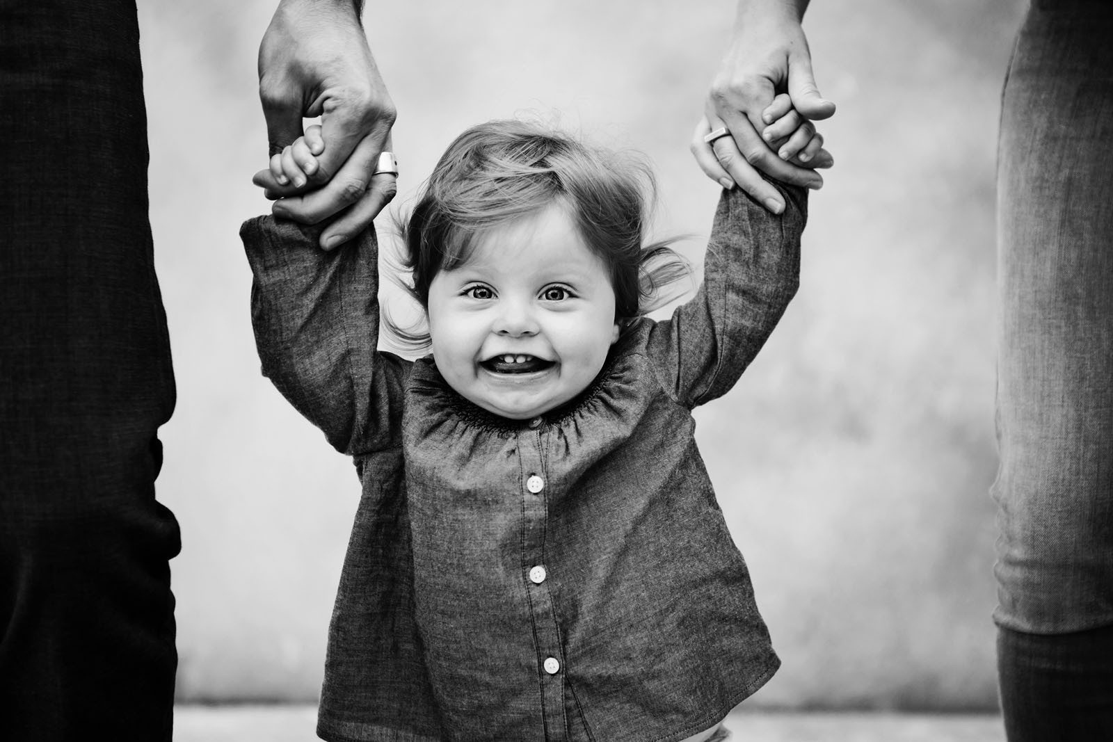 Image12 black and white photo of toddler holding parents hands lisa tichane