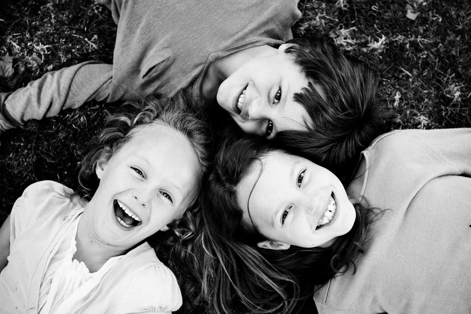 Image16 kids laying on ground with heads together smiling lisa tichane
