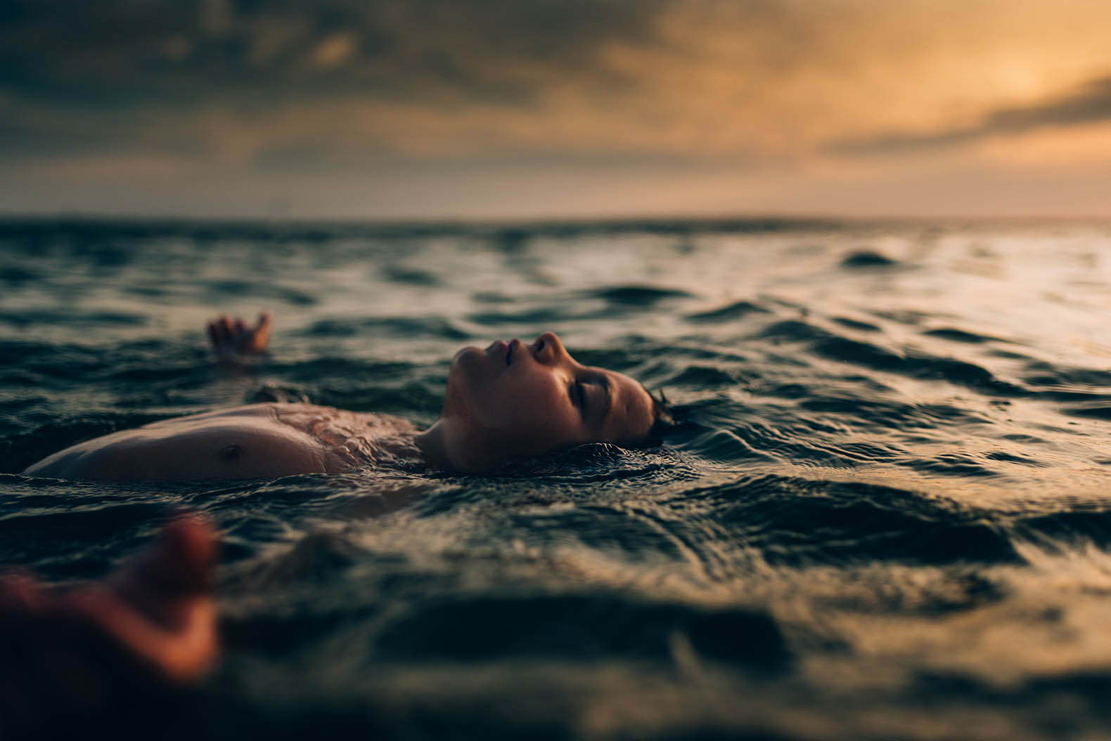 amber_talbert_child floating in open water at sunset
