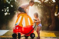 boy and girl playing with water hose and toy car at sunset amber talbert