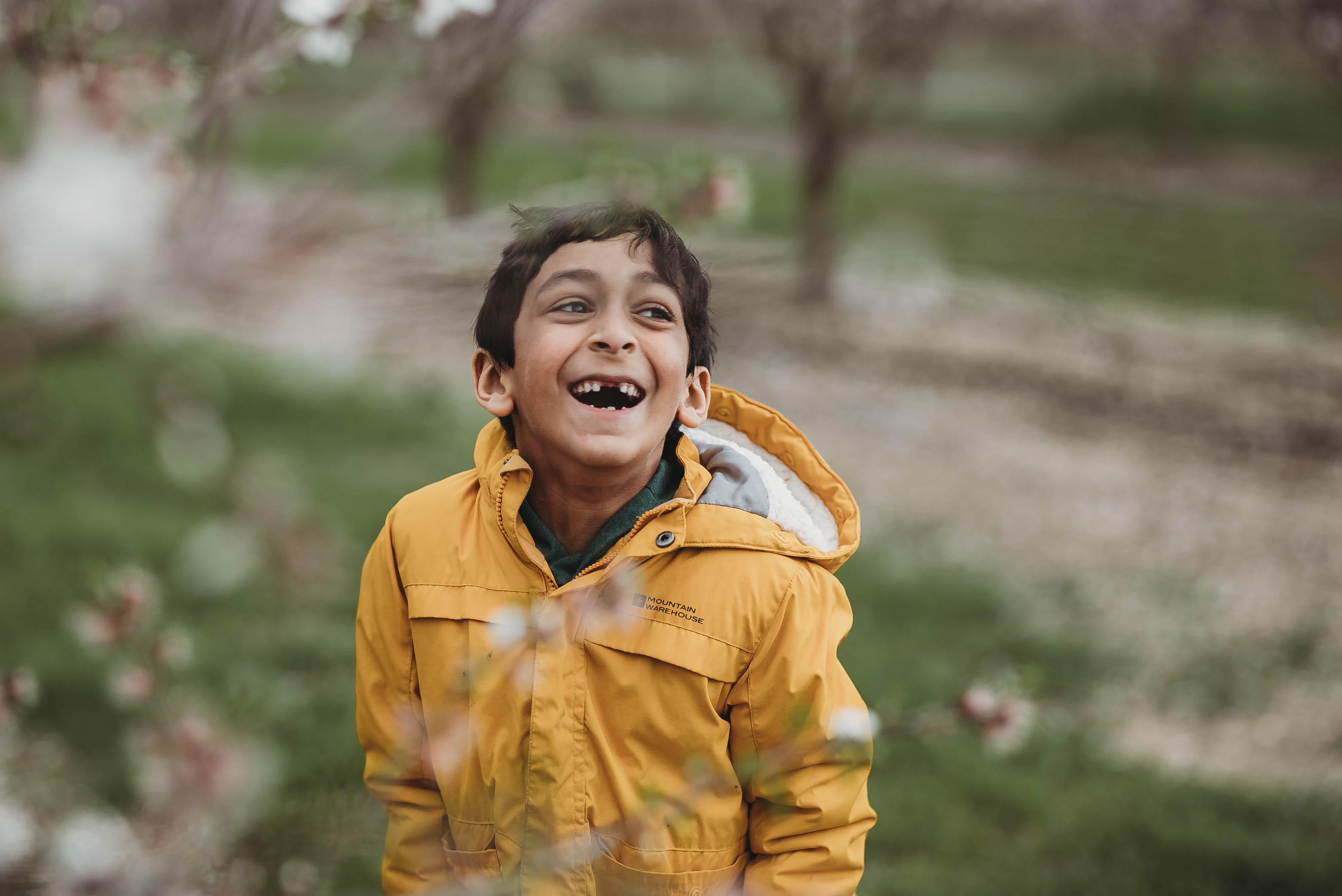 boy in yellow jacket laughing by jyo bhamadipati