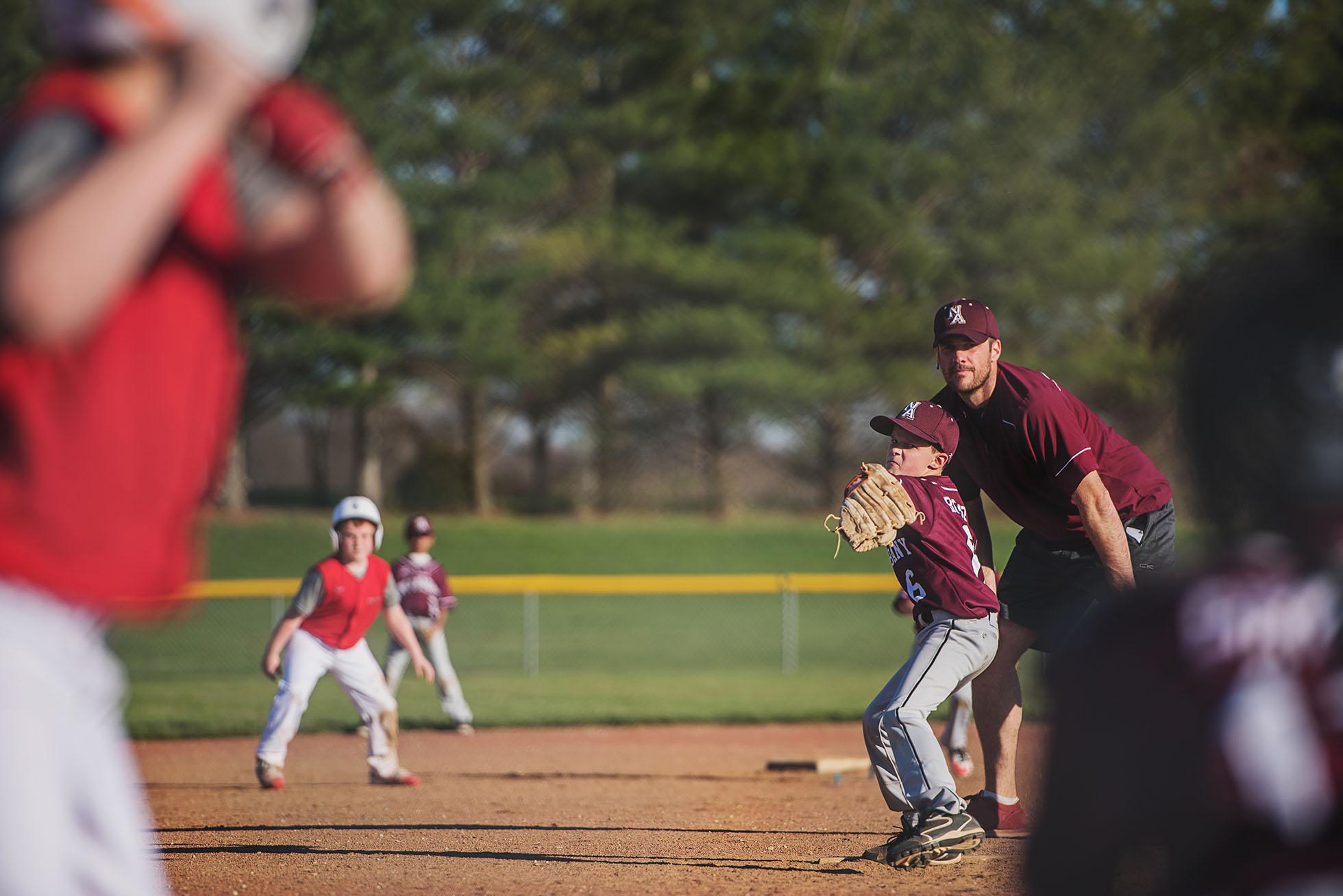 boy pitching baseball with coach behind him freezing motion kellie bieser