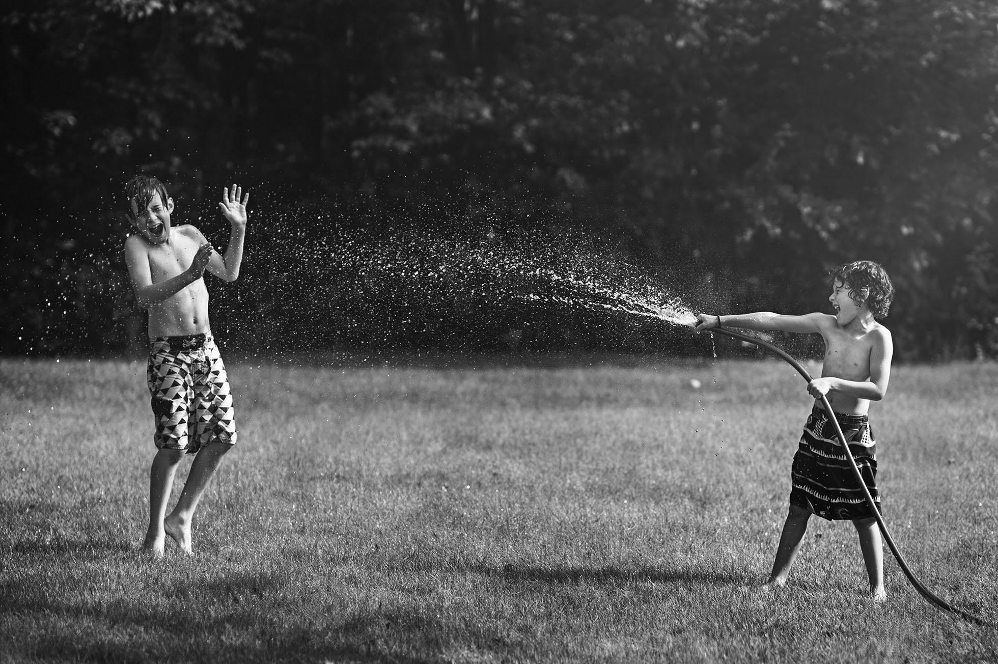 boy spraying brother with hose freezing motion kellie bieser