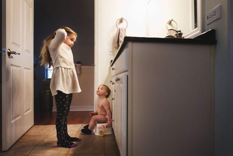 boy watching girl fix hair in bathroom kellie bieser
