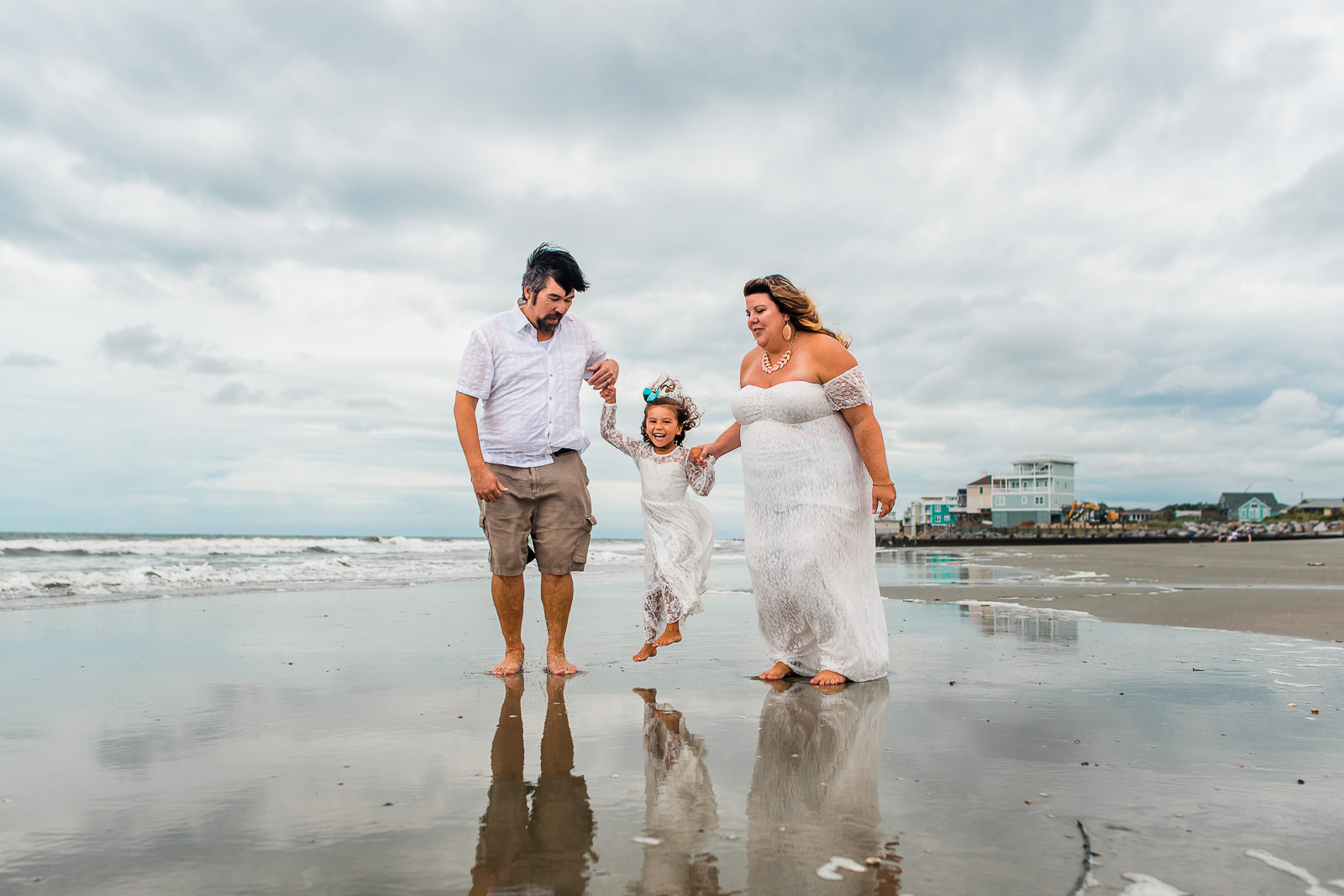 family-poses-mom-and-dad-swinging-daughter-on-beach_larissa-lord-photography-1-3