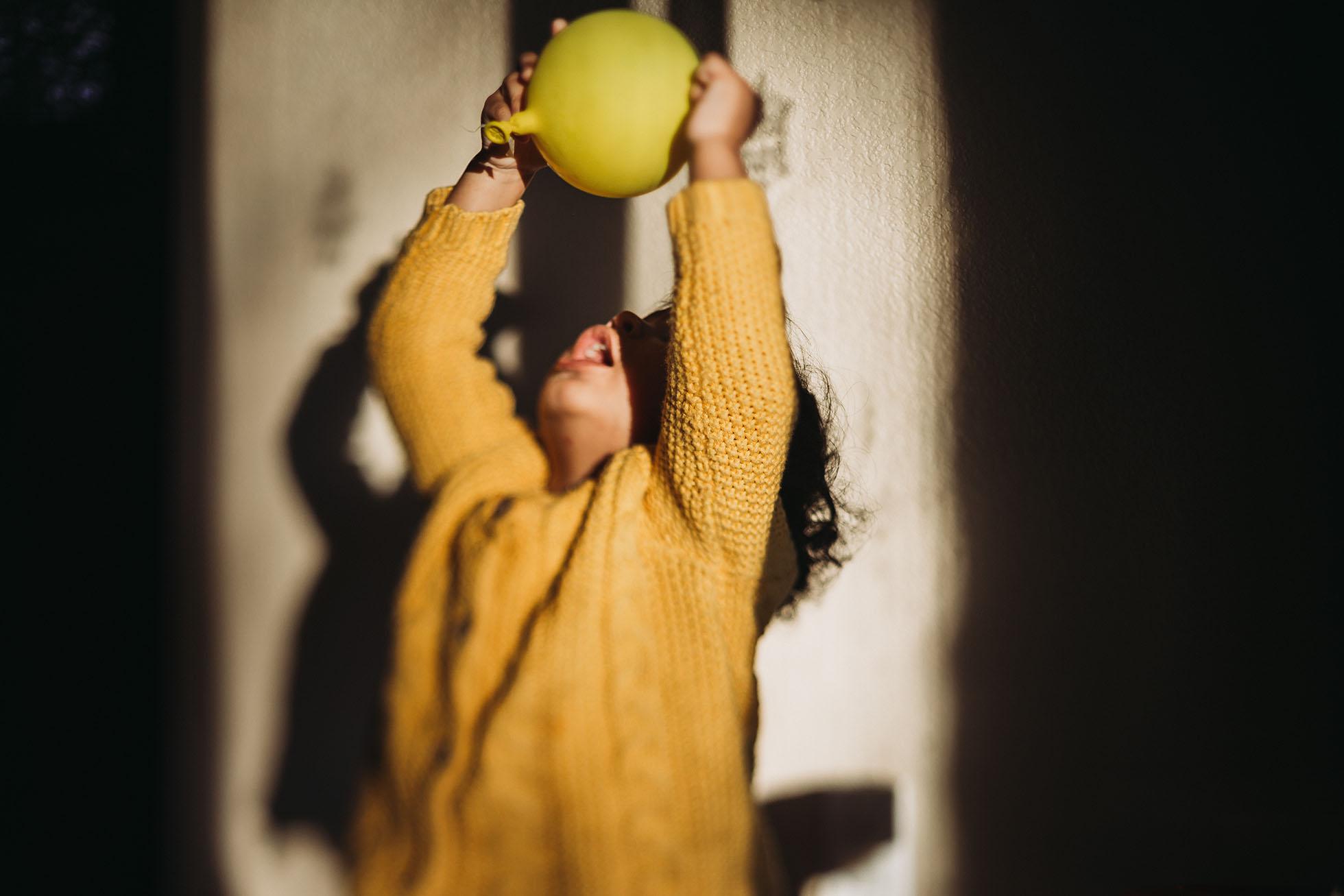 girl in yellow sweater playing with yellow balloon jyo bhamadipati