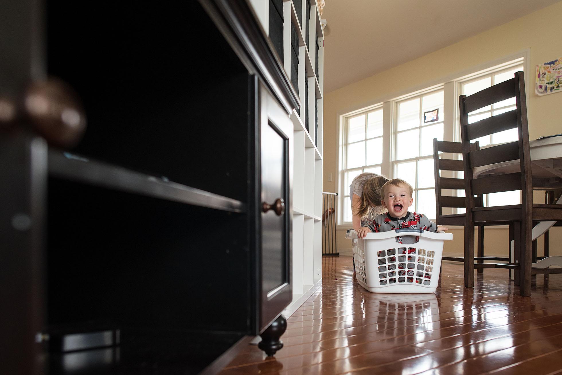 girl pushing toddler in laundry basket freezing motion kellie bieser