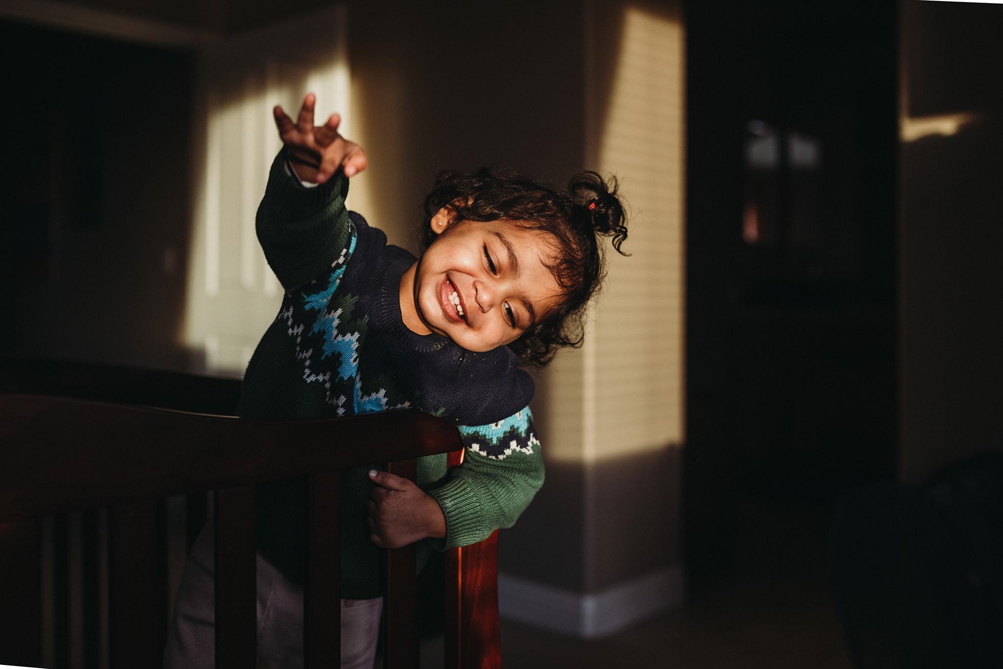 girl smiling in crib jyo bhamdipati
