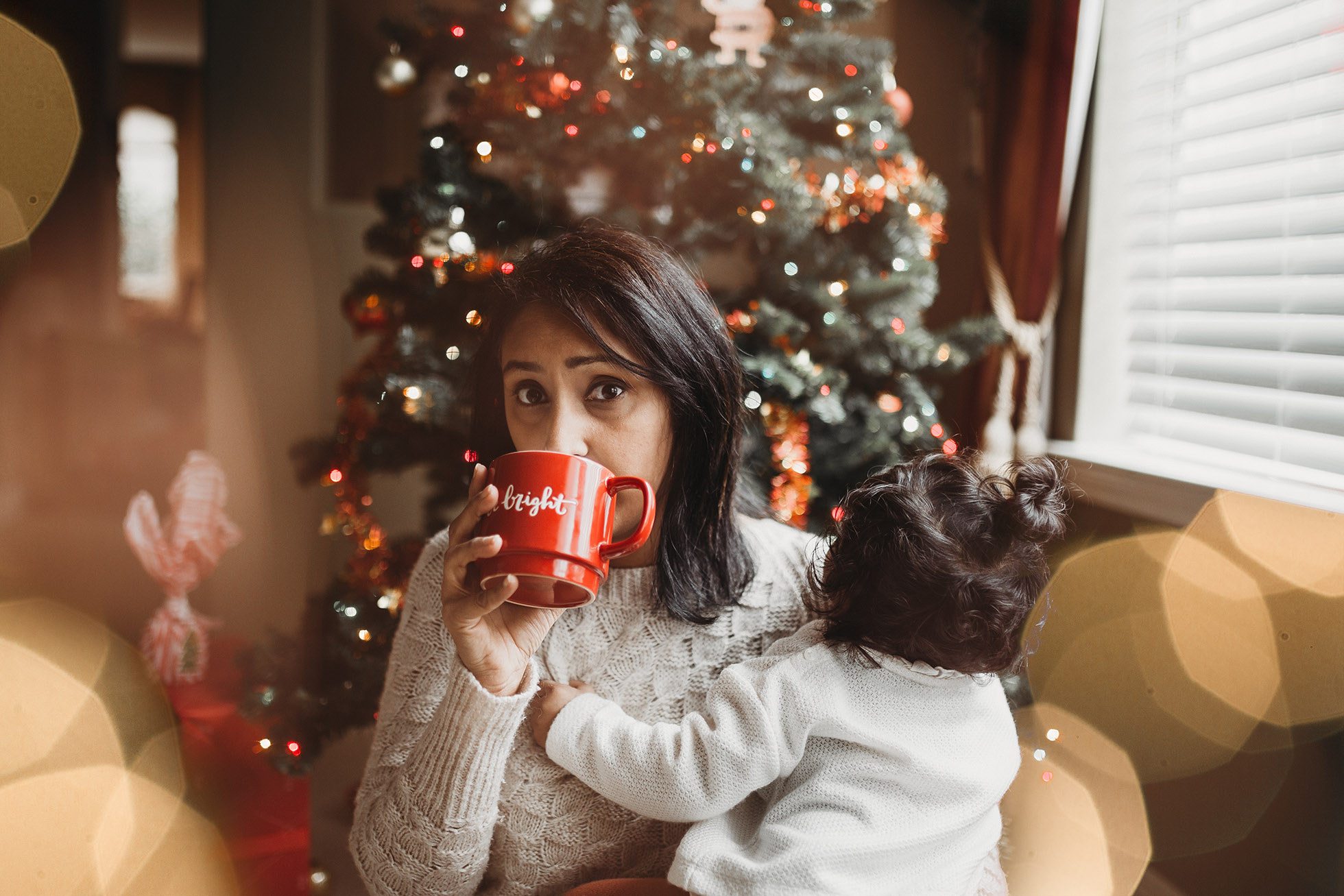 woman holding child and red coffee mug in front of christmas tree jyo bhamadipati