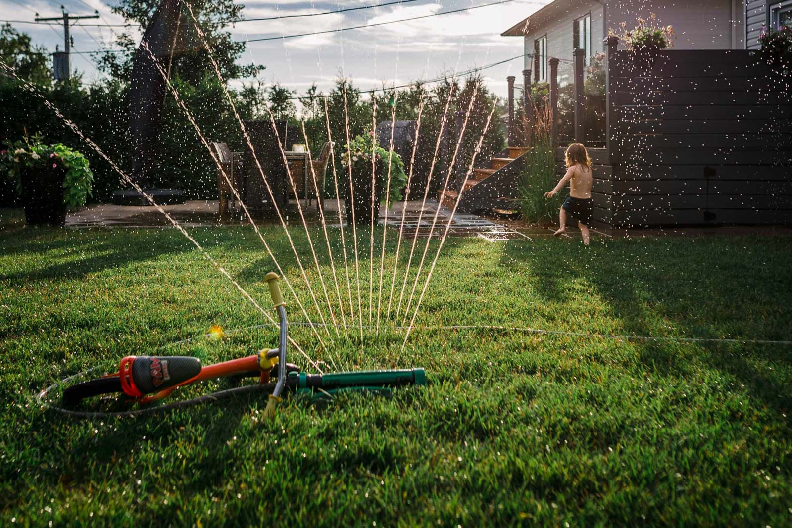 bike ride water hose toddler faceless running out splash golden hour backyard annick simon photographes paradis photographes documentaires quebec