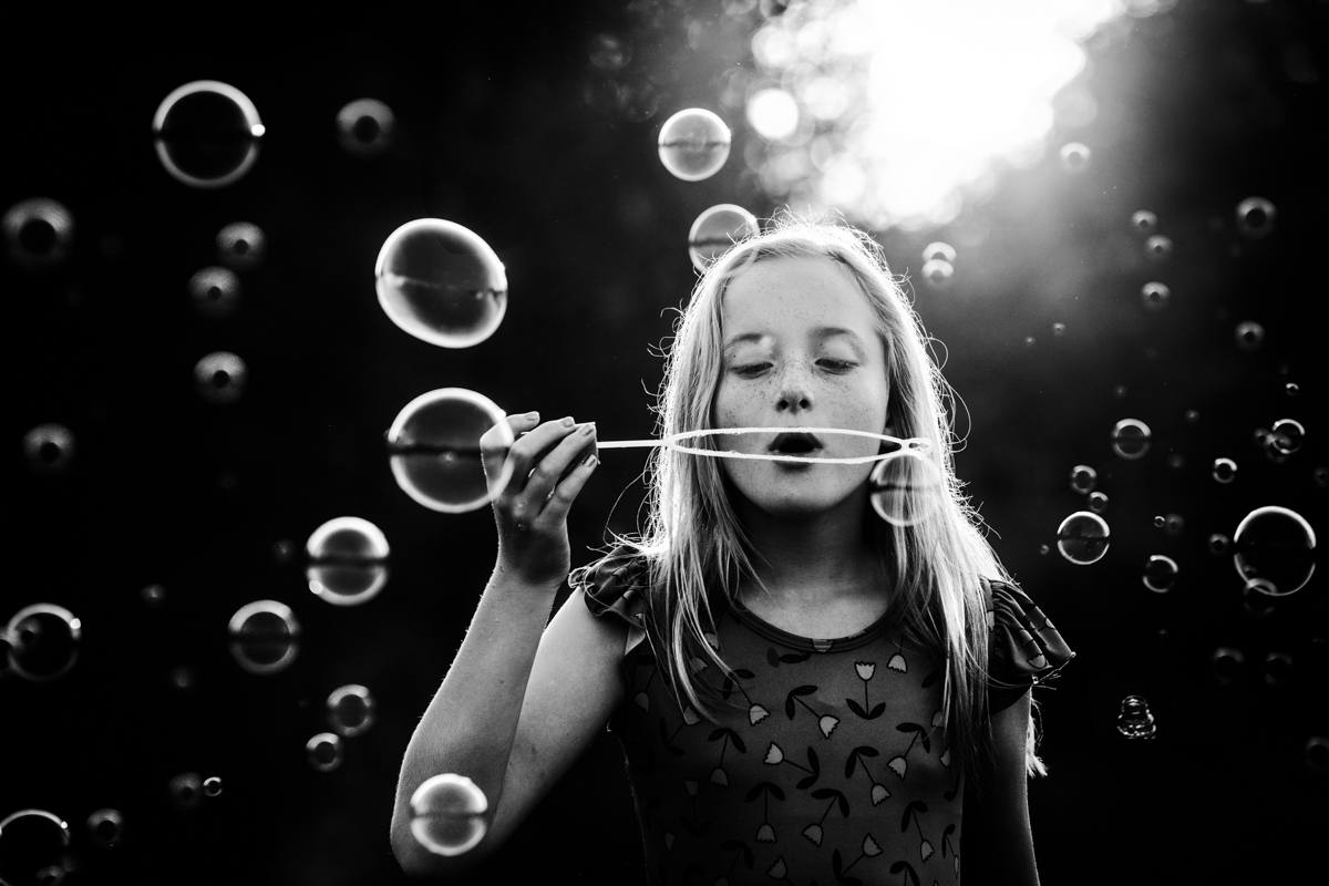 black and white photo of girl blowing bubbles by mickie devries
