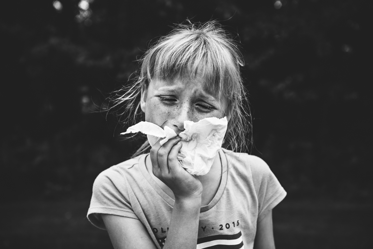 black and white photo of girl pulling out tooth by mickie devries