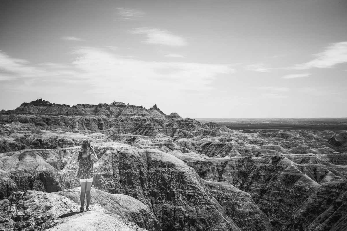 black and white photo of girl standing in mountain landscape by mickie devries