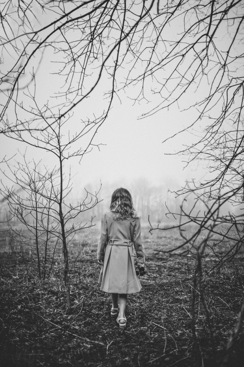 black and white photo of girl standing in woods by mickie devries