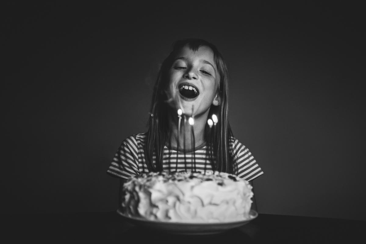 black and white photo of girl with birthday cake and candles smiling by mickie devries
