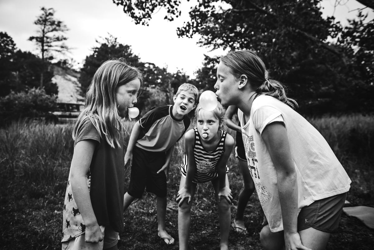 black and white photo of kids blowing bubble gum by mickie devries