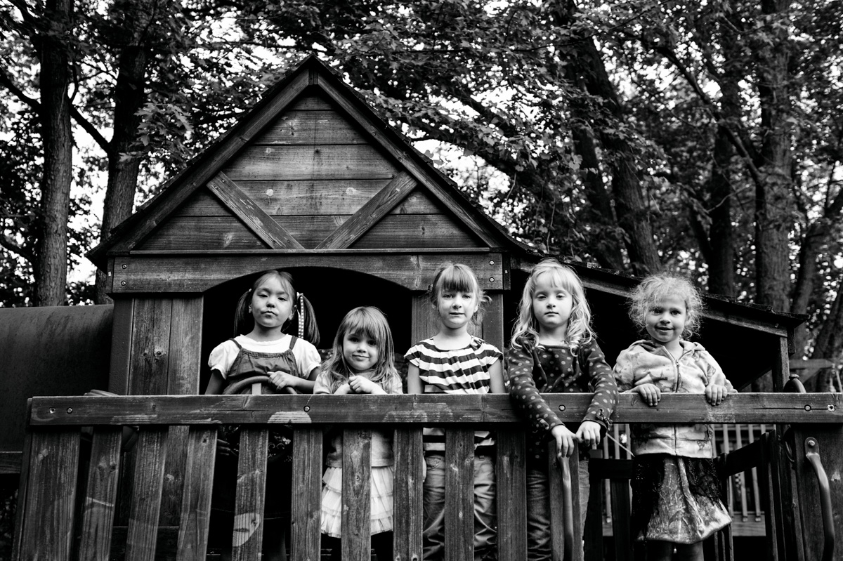 black and white photo of kids standing in front of tree house by mickie devries