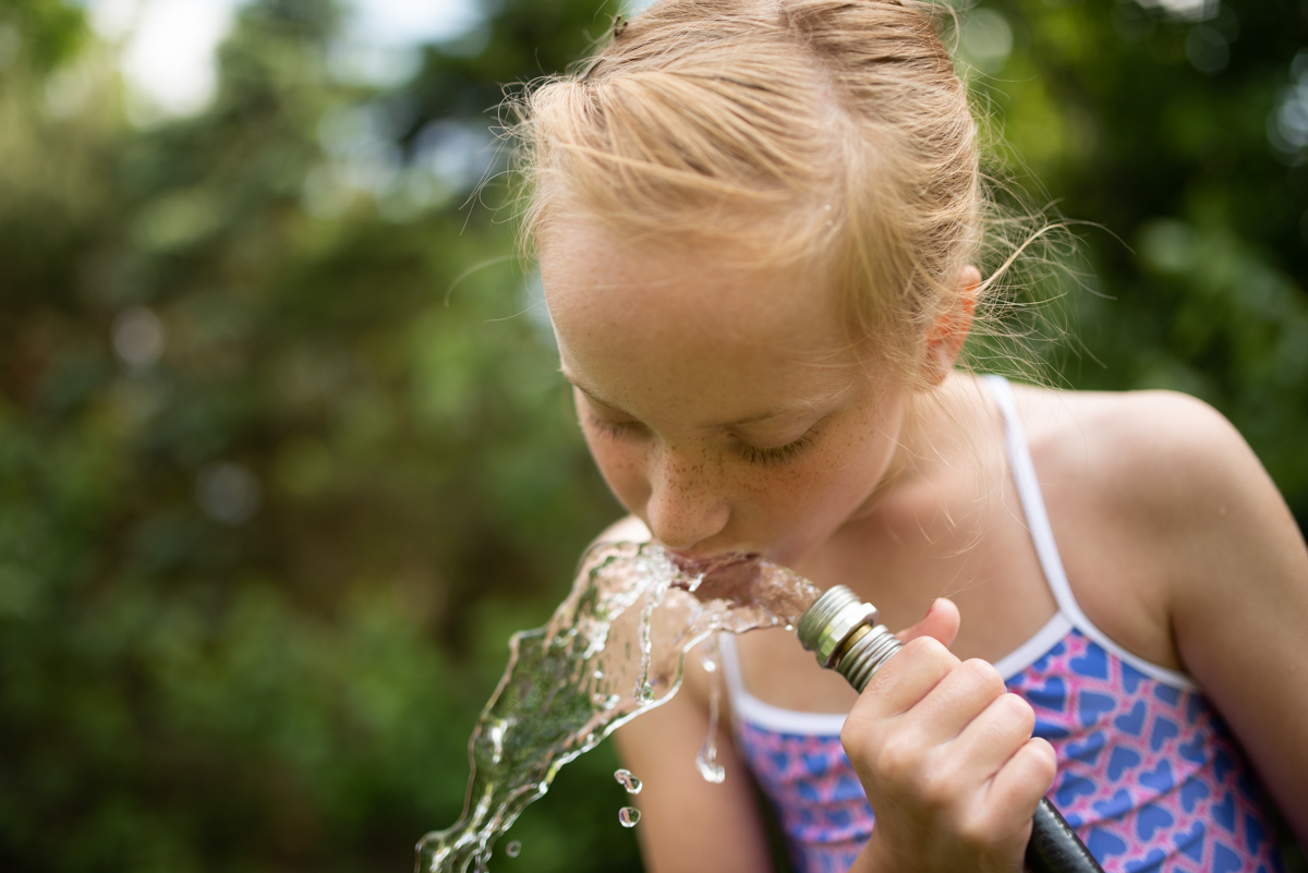 color photo of girl drinking water from hose by mickie devries