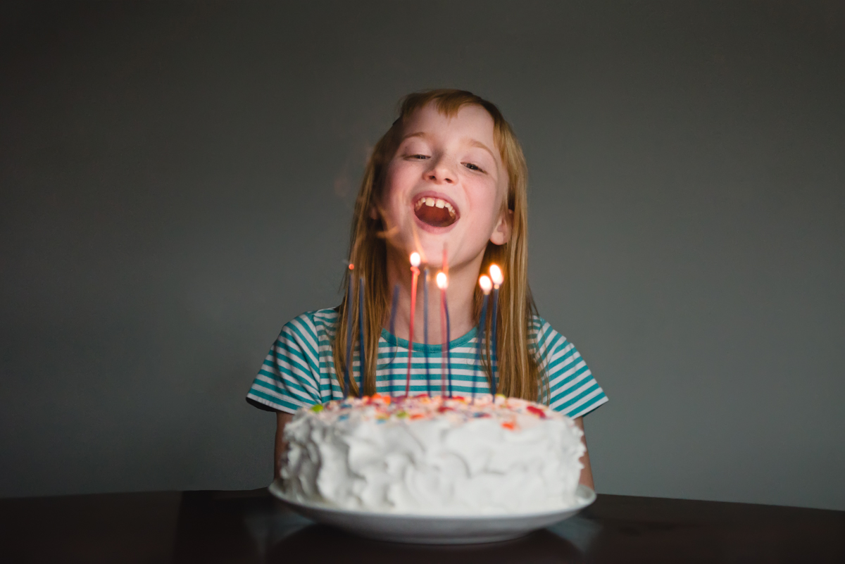 color photo of girl with birthday cake and candles smiling by mickie devries