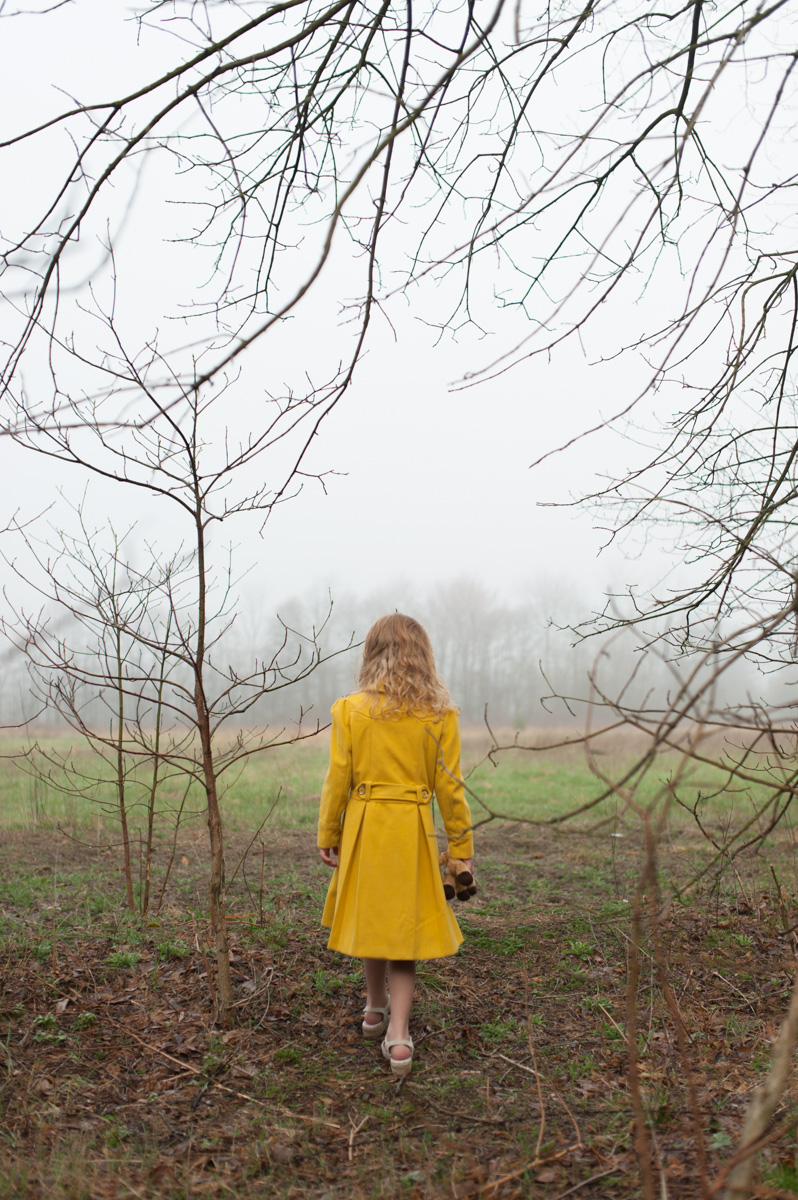 girl in yellow dress standing in woods by mickie devries