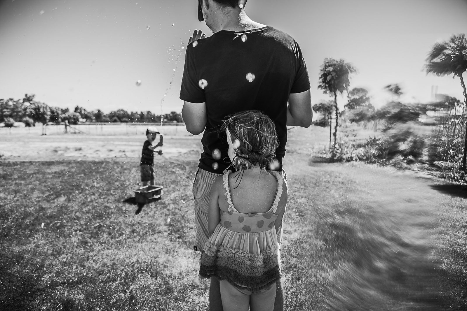 girl_hiding_behind_dad_in_water_pistol_fight_family_documentary_photographer_melbourne