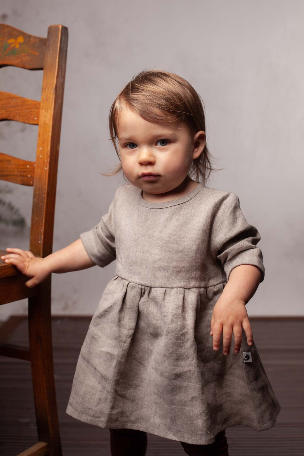 toddler in dress by chair by leah mcclean the-salted-image-noisy-forest-dress-portrait