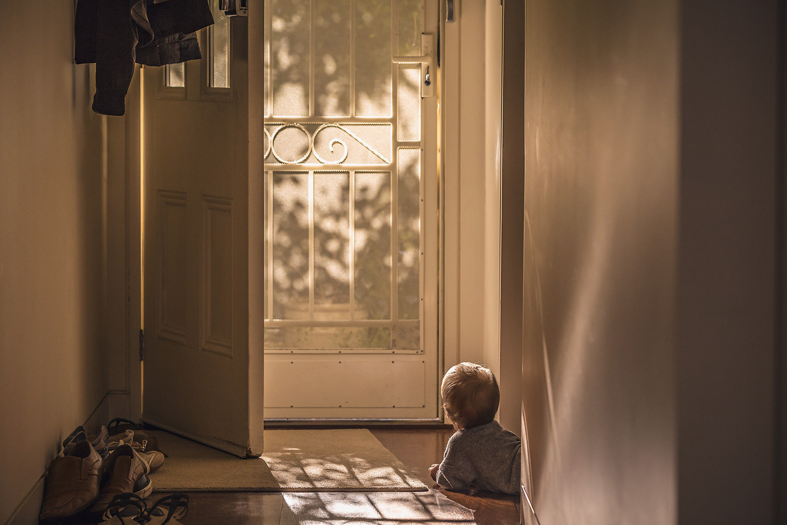 toddler looking out door with dappled light annick paradis