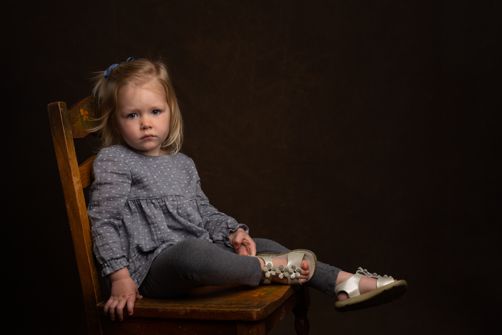 toddler on chair in front of dark background by leah mcclean The-Salted-Image-jobrett-childrens-clothing