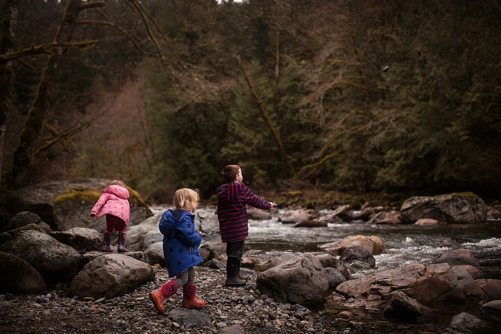 Outdoor_adventures_Neyssa_Lee_1 kids walking along rocky river bank in boots and coats
